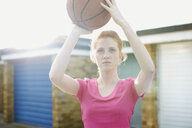 Portrait of woman holding basketball above head - CUF27361