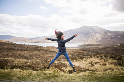 Mid adult woman in mountains doing star jump, Isle of Skye, Hebrides, Scotland - CUF27394