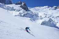 Mature female skier moving downhill on Mont Blanc massif, Graian Alps, France - CUF27433