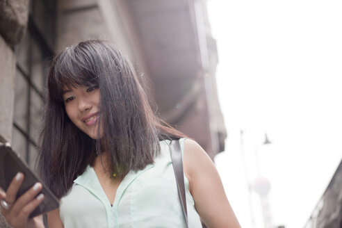 Young businesswoman, using smartphone, outdoors, Shanghai, China - CUF27502