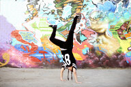 Young women in handstand breakdancing freeze against graffiti - CUF27601