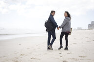 Rear view portrait of young couple strolling on beach, Western Cape, South Africa - CUF27715