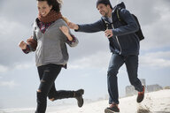 Young couple running and chasing on beach, Western Cape, South Africa - CUF27721