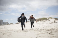 Young couple running on windswept beach, Western Cape, South Africa - CUF27724