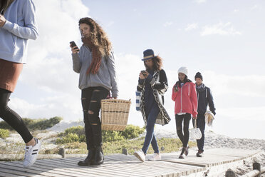 Row of young adult friends strolling along beach boardwalk reading smartphones, Western Cape, South Africa - CUF27727