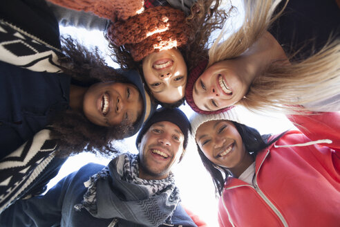 Low angle portrait of five happy adult friends huddled in a circle - CUF27730