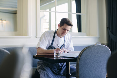 Young male chef writing up menu in restaurant - CUF27799