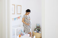 Pregnant mid adult woman looking down and touching stomach in childs nursery - CUF27820