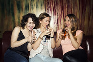 Three adult female friends drinking in bar - CUF27823
