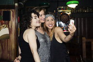 Three adult female friends taking smartphone selfie on night out in bar - CUF27826