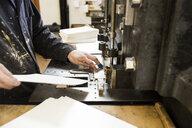 Male printer preparing paper for printing machinery in printing press workshop - CUF27962