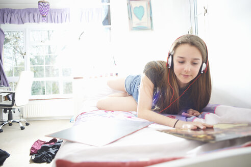 Teenage girl looking at vinyl record cover whilst listening to headphones in bedroom - CUF28117