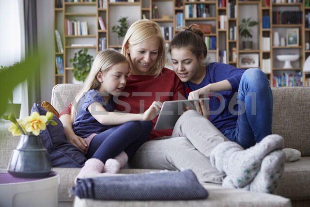 Mother and her daughters sitting on couch, having fun  using digital laptop - RBF06241 - Rainer Berg/Westend61