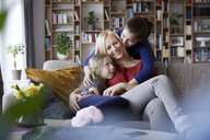 Mother and her daughters cuddling and having fun, sitting on couch - RBF06250