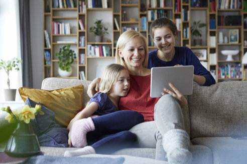 Mother and her daughters sitting on couch, having fun  using digital laptop - RBF06253