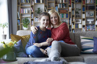 Mother and adolescent daughter sitting on couch with arms around - RBF06256