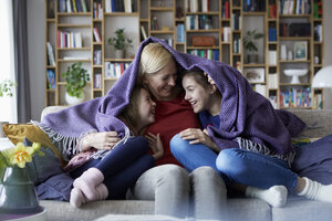 Mother and her daughters cuddling and having fun, sitting on couch, covered in blanket - RBF06259