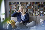 Woman relaxing at home, sitting on couch - RBF06262