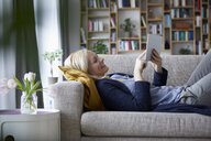 Woman using digital tablet, relaxing on couch - RBF06265