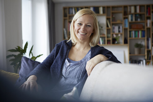 Woman relaxing at home, sitting on couch - RBF06268