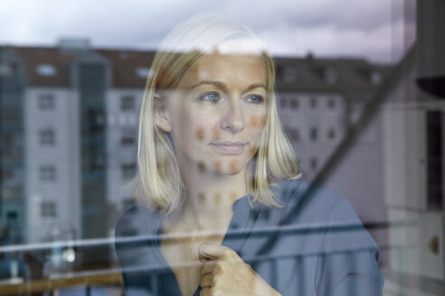 Blond woman looking out of window - RBF06277