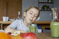 Girl sitting in kitchen, drinking homemade fruit smoothie - RBF06280