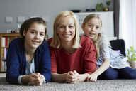 Happy mother and daughters having fun at home - RBF06283