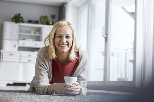 Happy woman relaxing at home, drinking coffee - RBF06286