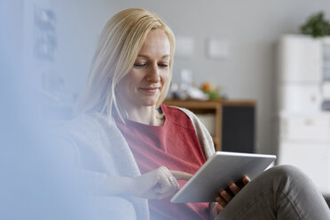 Blond woman sitting at home, using digital tablet - RBF06292