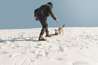 Man playing with dog in winter, having fun in the snow - REAF00272