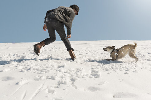 Man playing with dog in winter, throwing snow - REAF00275