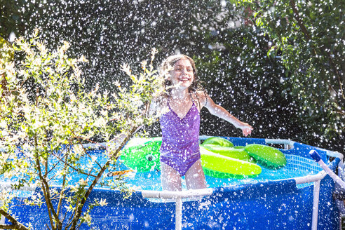 Laughing girl in paddling pool splashing with water - SARF03776