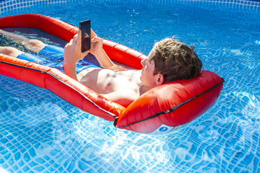 Boy floating on water in swimming pool using smartphone - SARF03779