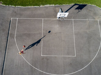 Aerial view of young woman playing basketball - STSF01606