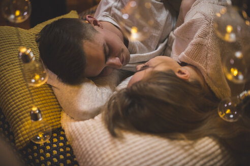 Romantic young couple cuddling in bed with fairy lights - AWF00048
