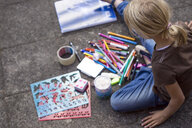 Girl sitting on pavement with many drawing materials - JFEF00871