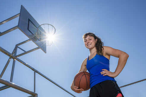 Young woman with basketball against the sun - STSF01611