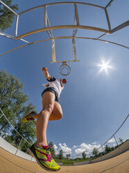 Young woman playing basketball against the sun - STSF01614