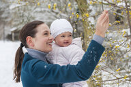 Portrait of happy mother with baby girl in snow-covered landscape - DIGF04572