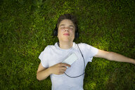 Portrait of boy lying on meadow listening music with headphones and smartphone - LVF07077