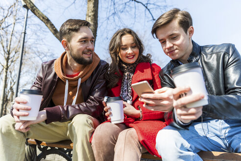 Russia, Moscow, group of friends at park, having fun together, drinking coffee and using phones - WPEF00401