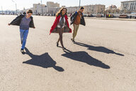 Russia, Moscow, group of friends having fun together and projecting airplane shaped shadows on the ground - WPEF00416
