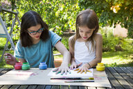 Sisters printing colour on sheet of paper with their hands - LVF07085