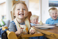 Three young children eating cake at tea table - CUF28638