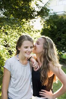 Two teenage girls whispering in garden - CUF28653