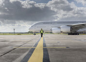Chief engineer walking from runway as A380 aircraft departs from airport - CUF28715