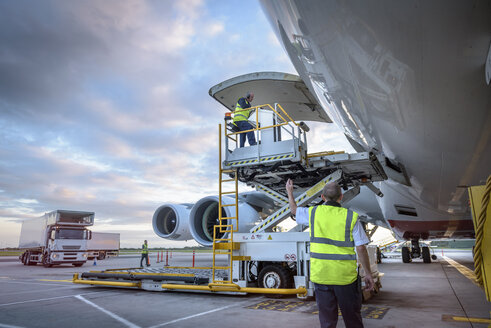 Ground crew attending to A380 aircraft with freight loader at airport - CUF28781
