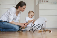 Mother and daughter assembling a chair at home - DIGF04584