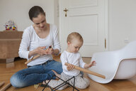 Mother and daughter assembling a chair at home - DIGF04587