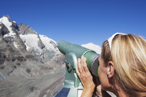 Austria, Carinthia, woman looking through binocular pointing at Grossglockner peak and Pasterze glacier, view from Kaiser-Franz-Josefs-Hoehe - GWF05531